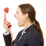 Gestresste Geschäftsfrau schreit ins Telefon